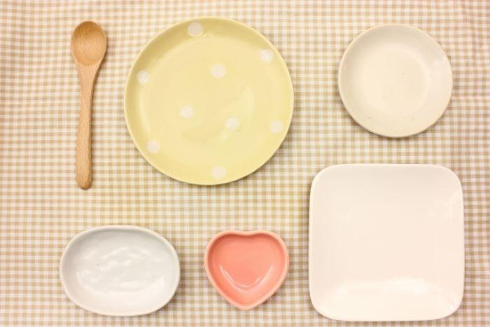 並んだ沢山のお皿とスプーンの写真