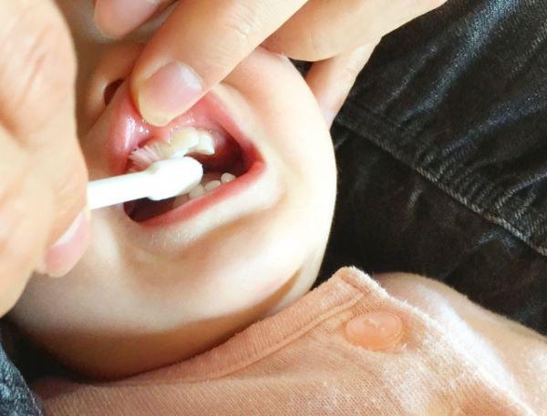 仕上げ歯磨きされる子どもの画像