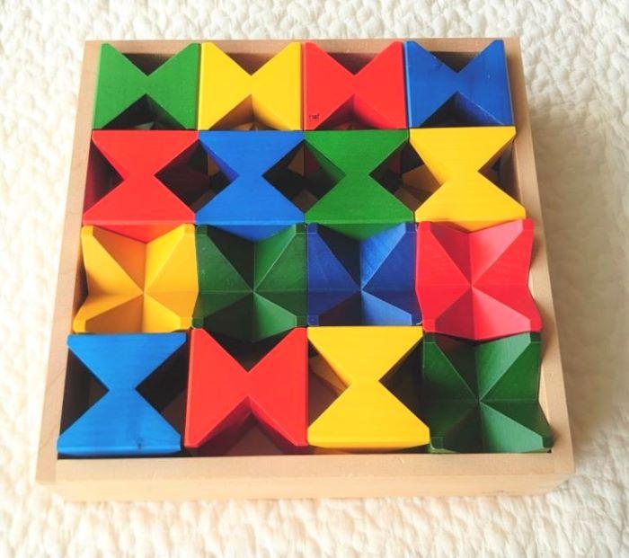 ランダムに並べられ木箱に収納された積み木の画像
