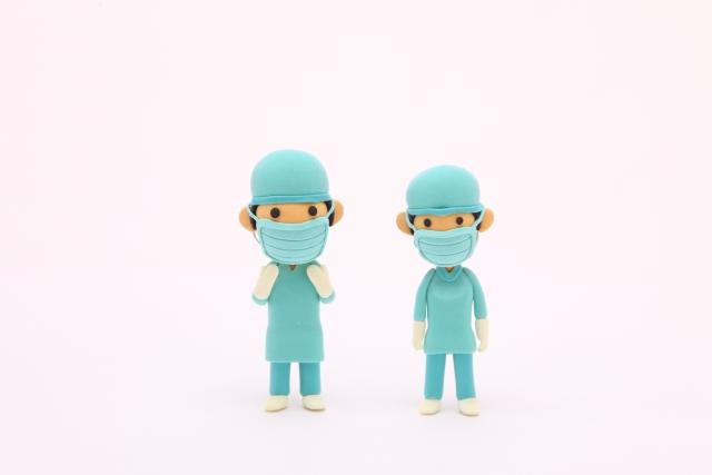 手術用ガウンを着た2人の紙粘土人形の医師の写真