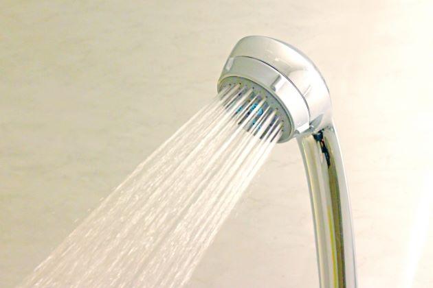 シャワーのヘッドから勢いよく出る水の写真