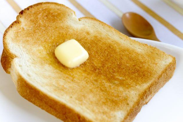 白い皿の上のバターを乗せたトーストの写真