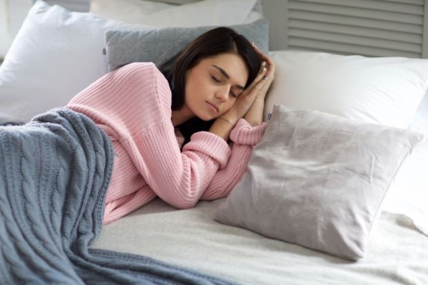 ベッドで眠るピンクの服を着た女性