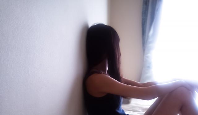壁に寄りかかり窓の外を眺める髪の長い女性