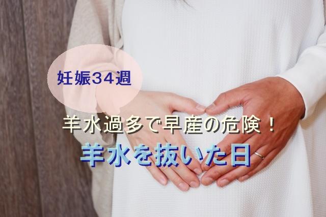 妊婦のお腹に手を手を当てた夫婦の写真